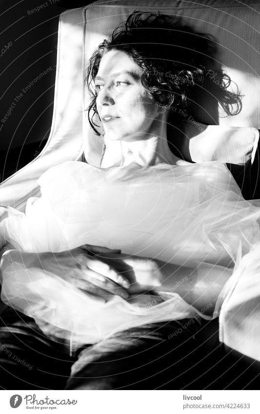 Frau lehnt an einem Sessel Gesicht Tüll Armsessel Lehnen zusammengerollt romantische Haltung Tüllkragen Licht & Schatten Sitz Innenbereich Porträt Lächeln Glück