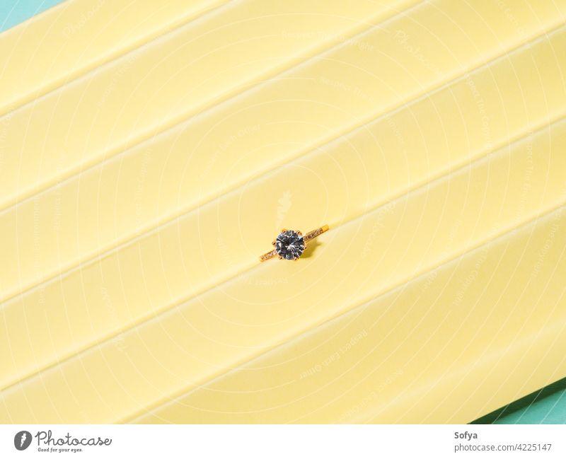 Glänzende Ring mit Edelstein auf gelbem Pastell Farbe Papier Hintergrund Schmuck gold Sammlung Frauen Accessoire golden Mode Juwel Design Geschenk Anzeige