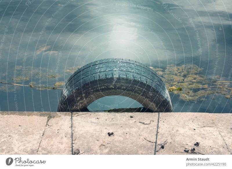 ein alter Autoreifen, der als Rammschutz in einem kleinen Hafen verwendet wird hafen Pier PKW Reifen Grunge Landen Wasser winken Beton Kunststoff Gummi