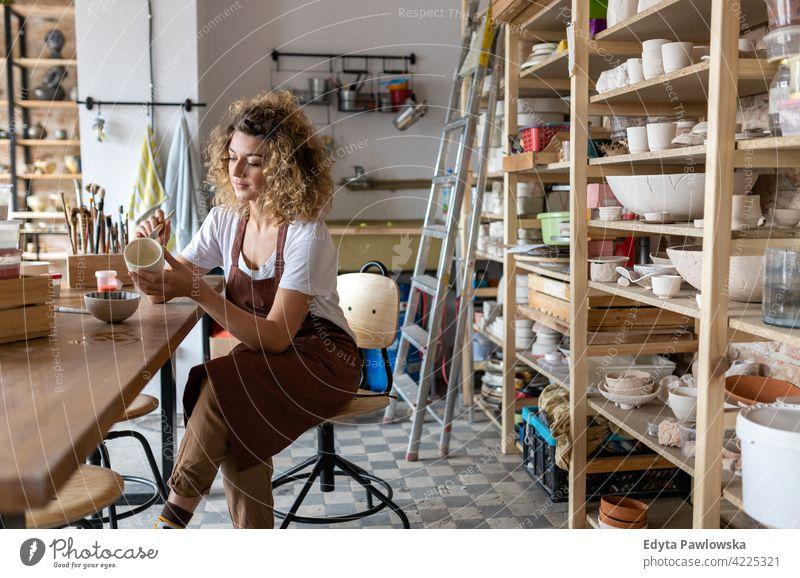 Kunsthandwerkerin bemalt eine Schale aus Ton im Kunstatelier Töpferwaren Künstler Keramik Arbeit arbeiten Menschen Frau jung Erwachsener lässig attraktiv Glück