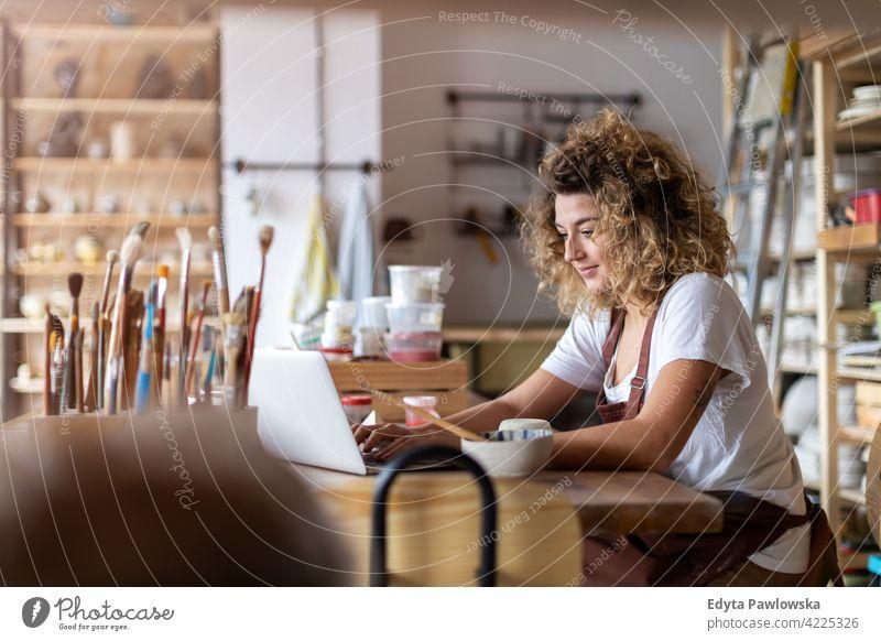 Frau Töpferin mit Laptop im Kunststudio Töpferwaren Künstler Keramik Arbeit arbeiten Menschen jung Erwachsener lässig attraktiv Glück Kaukasier genießend