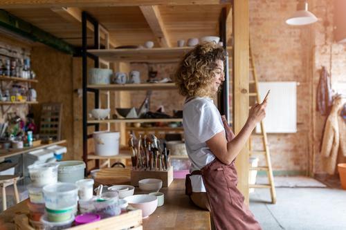 Töpferin mit Smartphone im Kunstatelier Töpferwaren Künstler Keramik Arbeit arbeiten Menschen Frau jung Erwachsener lässig attraktiv Glück Kaukasier genießend