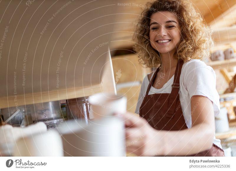 Porträt einer Töpferin im Kunstatelier Töpferwaren Künstler Keramik Arbeit arbeiten Menschen Frau jung Erwachsener lässig attraktiv Glück Kaukasier genießend