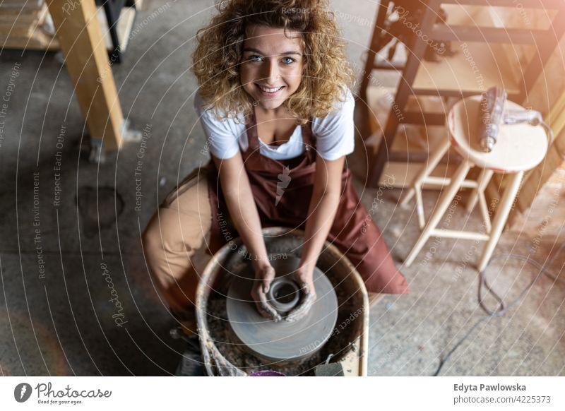 Frau macht Keramikarbeit mit Töpferscheibe Töpferwaren Künstler Kunst Arbeit arbeiten Menschen jung Erwachsener lässig attraktiv Glück Kaukasier genießend