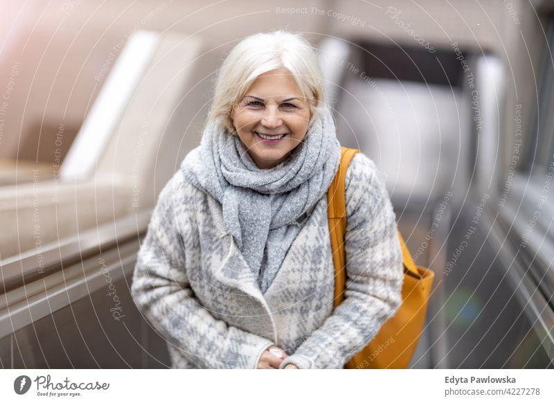Glückliche Seniorin auf Rolltreppe Brille Lächeln genießend entspannt Positivität selbstbewusst natürlich Senioren Rentnerin Rentnerinnen Frau lässig im Freien