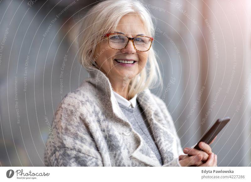 Porträt einer älteren Frau, die ein Mobiltelefon benutzt Brille Glück Lächeln genießend entspannt Positivität selbstbewusst natürlich Senior Senioren Rentnerin