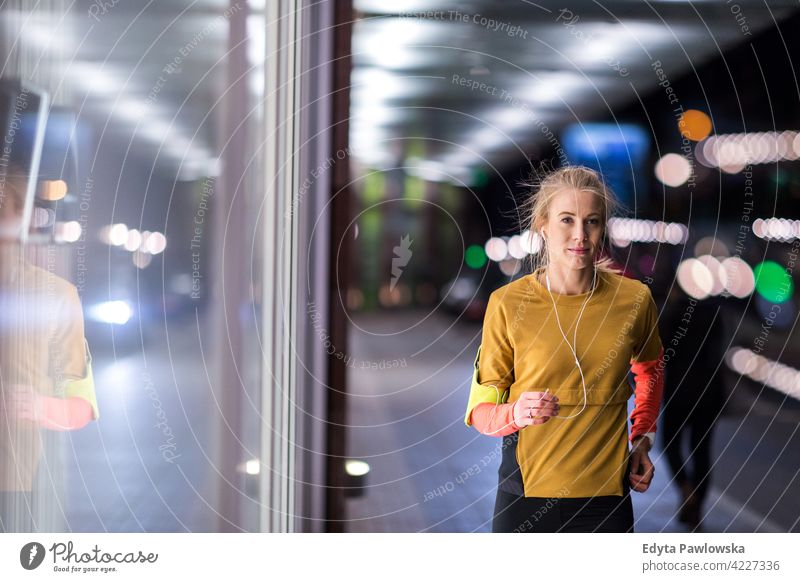 Weibliche Läuferin in der Stadt bei Nacht Jogger Joggen rennen Energie Übung Bekleidung trainiert. Fitness Erholung Sport Aktivität Vitalität Körper