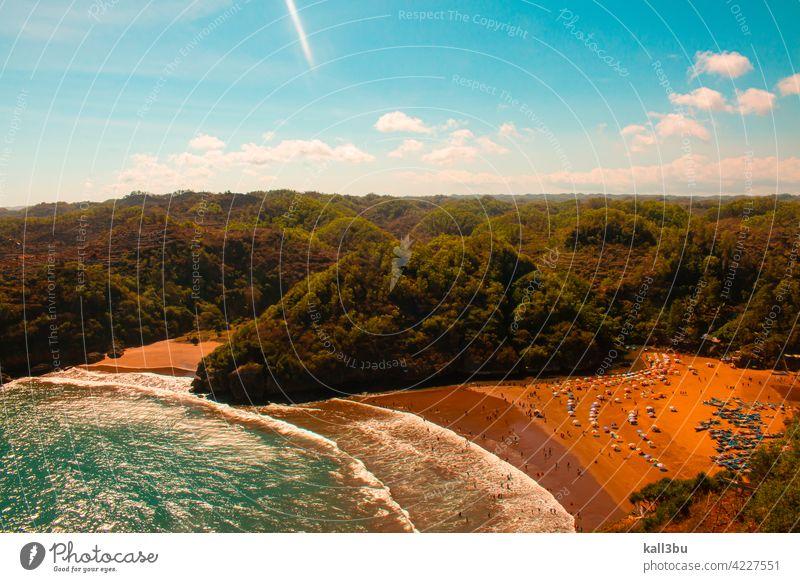 Lagunenstrand Baron auf der Insel Java in Indonesien, flankiert von grünen Bergen. Sand Strand Sonnenschirme farbenfroh Schwimmsport MEER Hochwinkelansicht