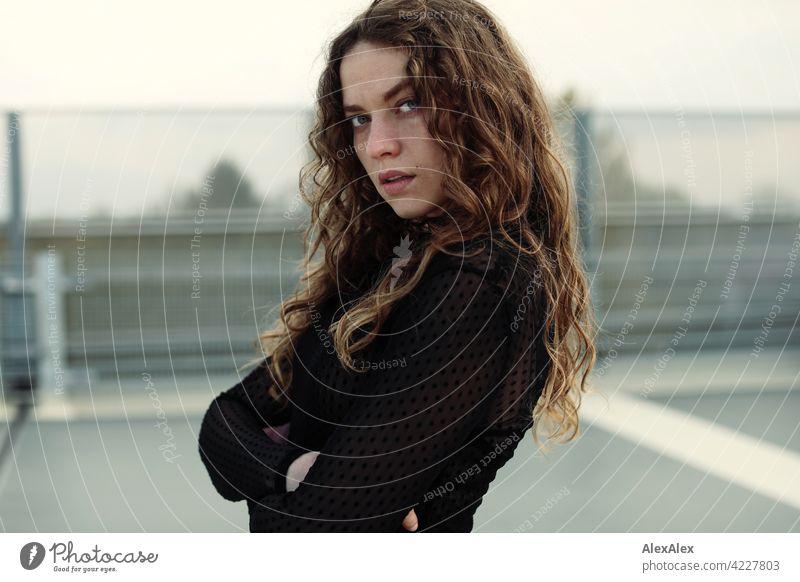 Portrait einer jungen Frau mit langem, brünettem, lockigem Haar auf dem obersten Parkdeck eines Parkhauses junge Frau 18-30 Jahre schön Schönheit Haare