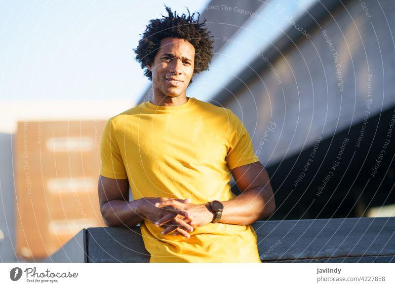 Schwarzer Mann mit Afro-Haar nimmt eine Pause nach dem Training. Fitness schwarz ruhen anstrengen Läufer Übung Jogger männlich Sport außerhalb copyspace Typ