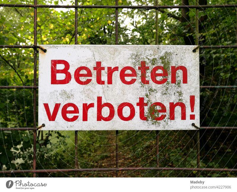 Betreten verboten Schild am rostigen Drahtgitter eines Hoftor in Oerlinghausen bei Bielefeld am Hermannsweg im Teutoburger Wald in Ostwestfalen-Lippe schild