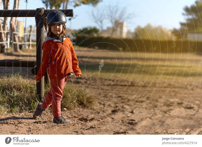 4 Jahre altes Mädchen in Reiten gekleidet und bereit zu reiten mit schönen Haltung und Sonnenstrahl. Umgebung gemischt zwischen ländlichen und städtischen Tier