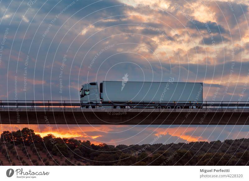 Kühltransporter, der über eine Brücke mit einem dramatischen Himmel im Hintergrund fährt. Straße Lastwagen Anhänger Transport gekühlt Sonnenuntergang Viadukt
