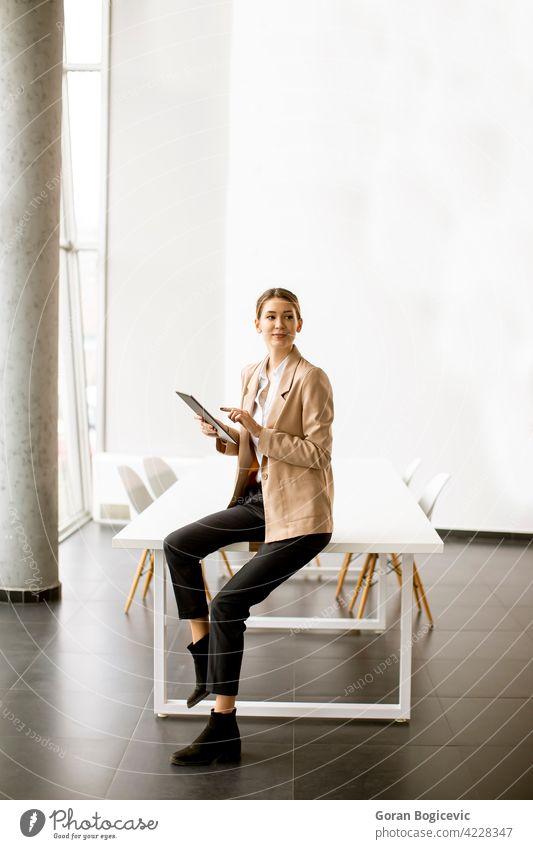 Junge Frau hält digitales Tablet in modernem Büro Erwachsener attraktiv schön Business Geschäftsfrauen Anzeige elektronisch Glück Beteiligung im Innenbereich
