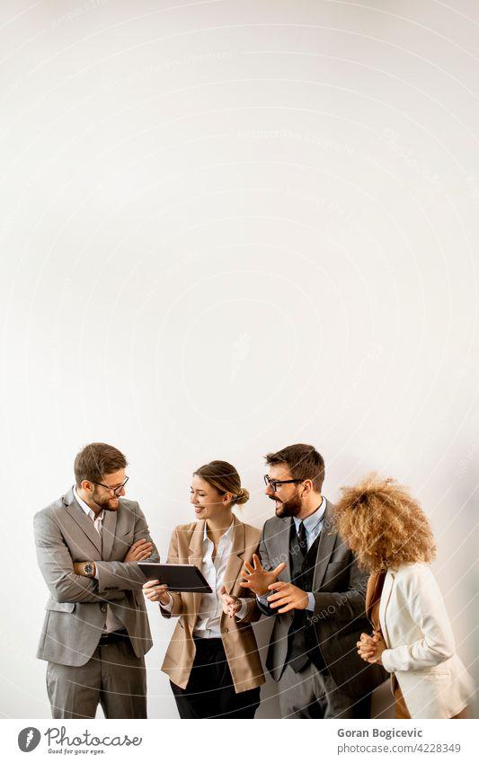 Multiethnische Geschäftsleute, die ein digitales Tablet benutzen, während sie an der Wand im Büro stehen Erwachsener Afrikanisch Amerikaner schwarz Business