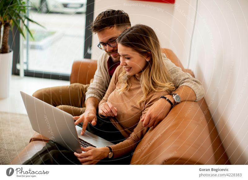 Junges Paar mit Laptop zusammen, während auf dem Sofa zu Hause sitzen Erwachsener Appartement attraktiv Freund sorgenfrei Kaukasier bequem Computer Liege Tag