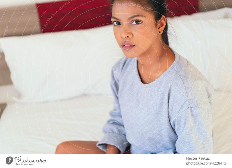 Eine attraktive junge Frau sitzt auf ihrem Schlafzimmerbett. Sie schaut in die Kamera schwarz Afrikanisch Glück Porträt Erholung Bett Menschen Schönheit Frauen