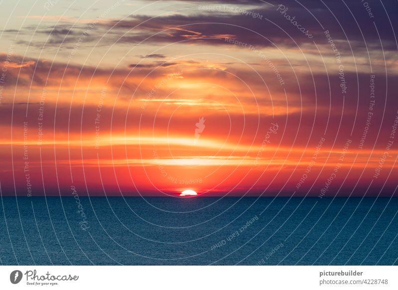 Sonnenuntergang über dem Meer mit schönem Farbenspiel Nordsee Wasser Himmel Wolken Wellen Abend Sonnenlicht Horizont Dämmerung Licht rot gelb blau orange