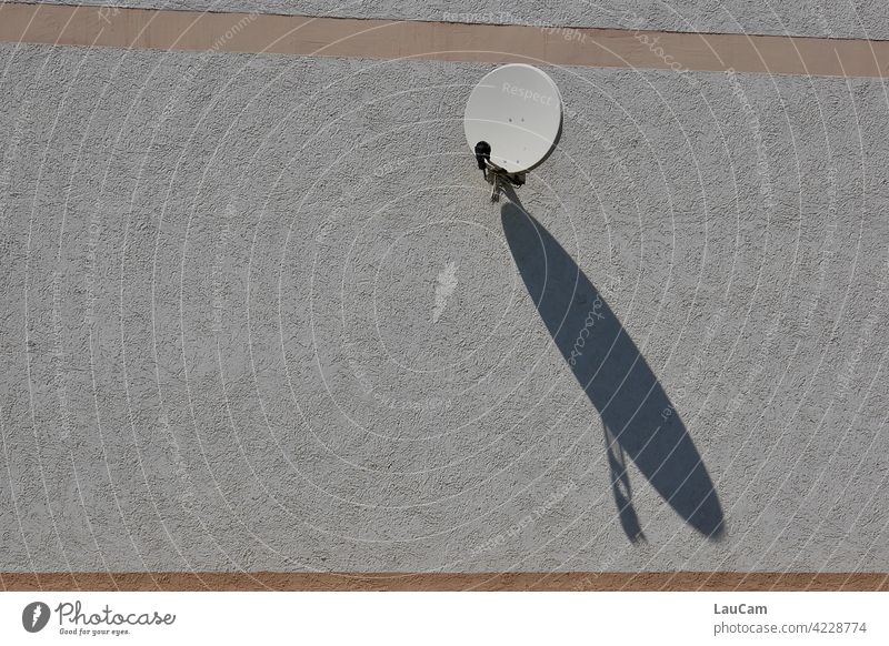Kleine Satellitenschüssel mit großem Schattenspiel Fassade Hausfassade Sonne Sonnenlicht Schattenwurf klein Kommunikation Television Empfang empfangsbereit
