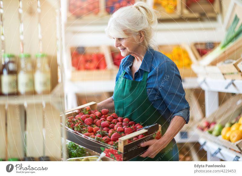 Ältere Frau arbeitet in einem kleinen Lebensmittelladen Lebensmittelhändler Gemüsehändler Lebensmittelgeschäft Menschen Senior reif Erwachsener lässig attraktiv