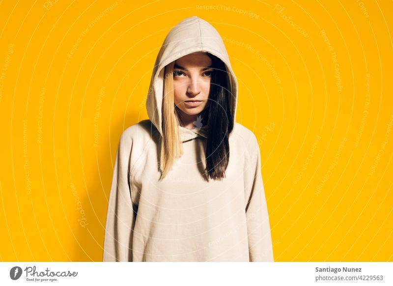 Junges Mädchen Porträt Atelier gelber Hintergrund in die Kamera schauen Ausdruck farbenfroh Frisur lässig jung Frau ernst zwei Farben Haar im Innenbereich schön