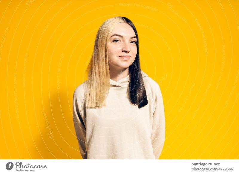 Junges Mädchen Porträt Kapuzenpulli Lächeln niedlich Unschuld heiter Glück Fröhlichkeit Atelier gelber Hintergrund in die Kamera schauen Ausdruck farbenfroh