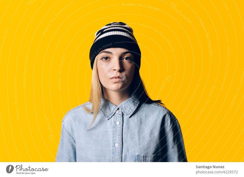 Mädchen trägt Hut Porträt Atelier gelber Hintergrund in die Kamera schauen Ausdruck farbenfroh Frisur lässig jung Frau ernst zwei Farben Haar im Innenbereich