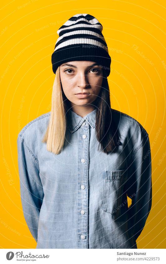 Serious Girl Wearing Hat Portrait Atelier gelber Hintergrund Porträt in die Kamera schauen Ausdruck farbenfroh Frisur lässig jung Mädchen Frau ernst