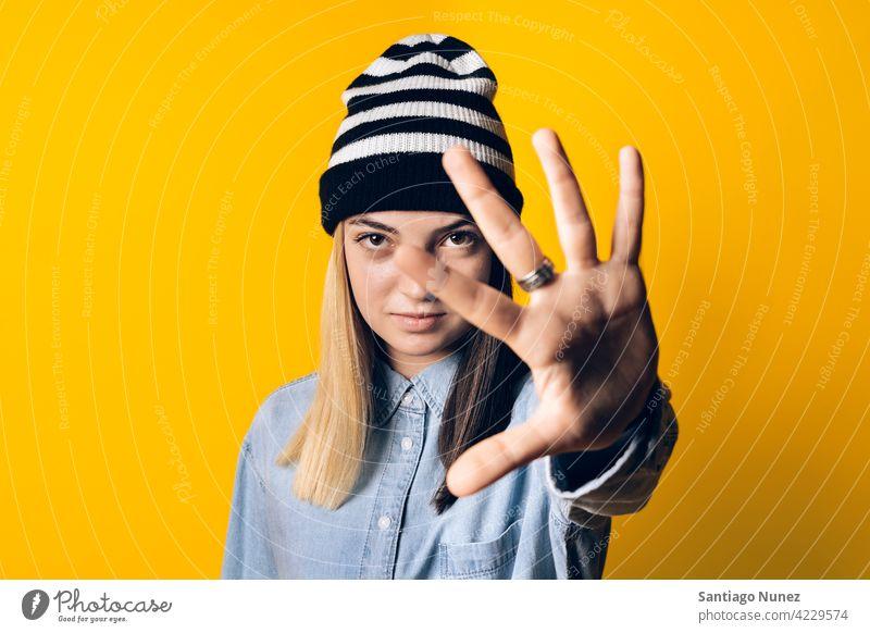 Ausdrucksstarkes junges Mädchen Porträt Atelier gelber Hintergrund in die Kamera schauen farbenfroh Frisur lässig Frau ernst zwei Farben Haar im Innenbereich