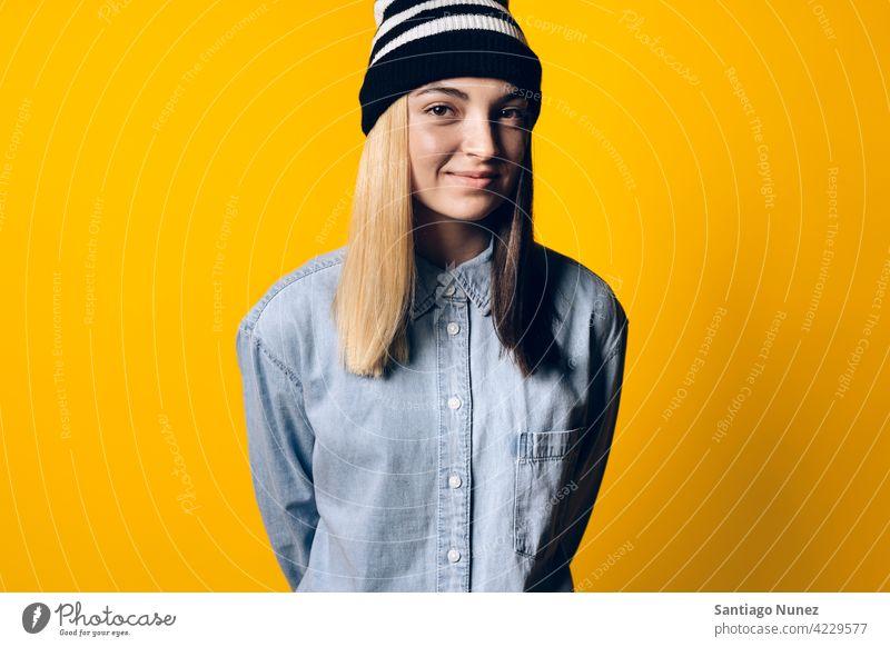 Glückliches Mädchen trägt Hut Porträt Lächeln niedlich Unschuld heiter Fröhlichkeit Atelier gelber Hintergrund in die Kamera schauen Ausdruck farbenfroh Frisur