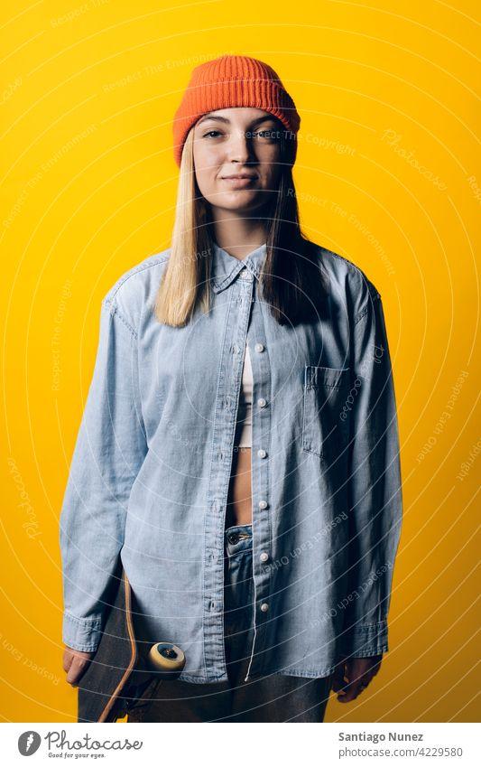 Cooles junges Mädchen Porträt Atelier gelber Hintergrund in die Kamera schauen Ausdruck farbenfroh Frisur lässig Frau ernst zwei Farben Haar im Innenbereich