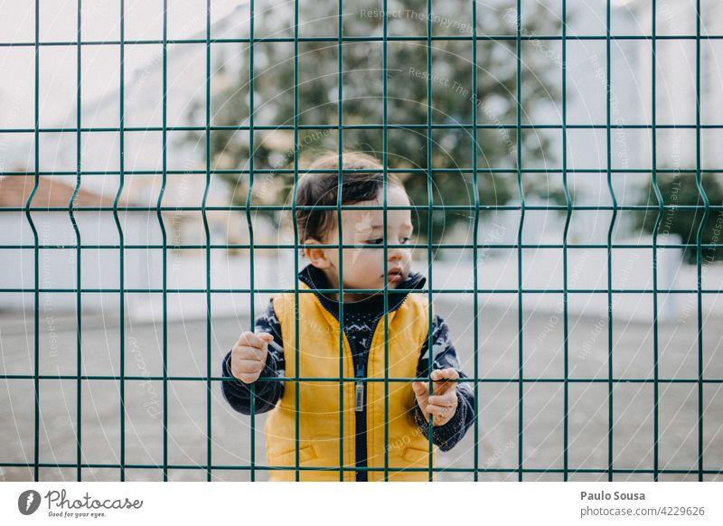 Kind hinter Zaun 1-3 Jahre Junge hinten Barriere maskulin Außenaufnahme Kleinkind Mensch Farbfoto Tag Porträt Schule Kindergarten Blick Kindheit