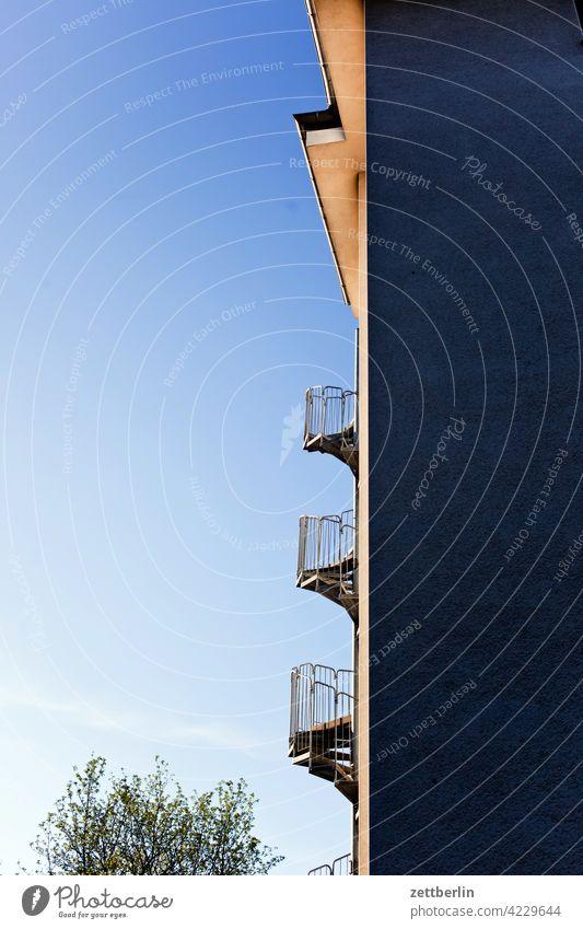 Außentreppe im Morgenlicht außentreppe wendeltreppe feuerschutz fluchtweg brandschutz haus wand hauswand fassade ecke winkel froschperspektive himmel wolkenlos