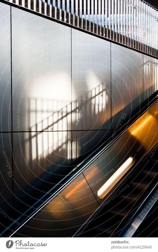 Rolltreppe rolltreppe aufwärts abwärts bahnhof bahnsteig verkehr öpnv wand wandverkleidung metall glanz geländer licht schatten handlauf beleuchtung schräg