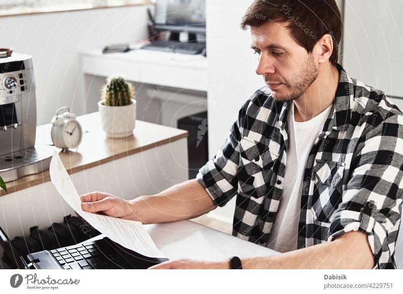 Mann arbeitet im Home Office mit Laptop und Dokumenten Business Büro Arbeitsplatz im Innenbereich Computer Laptop-Geschäft Porträt Geschäftsmann lässig