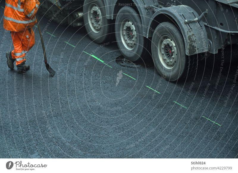 Arbeiter in orangefarbener Warnkleidung stützt sich auf Schaufel, steht neben LKW- Asphalt asphaltieren Straßenbau Pause Arbeitspause faulenzen geruhsam Strich