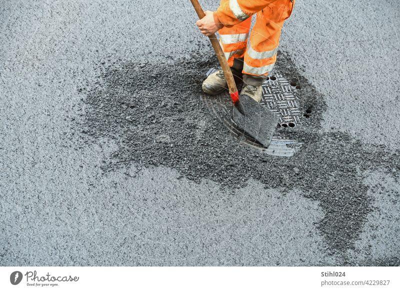Straßenbauarbeiter mit orangener Arbeitsbekleidung und Schaufel strassenarbeiter schaufel hose reflektierend arbeiten kanaldeckel asphaltarbeiten sanieren