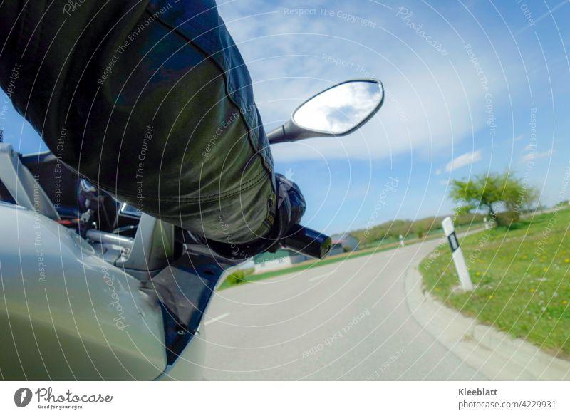 Kurvenlust - Kurvenfahrt auf einem Motorrad aus der Sicht des Sozius bei schönem Frühlingswetter Motorrad fahren Motorradfahrer Teilausschnitt Hand am Lenker