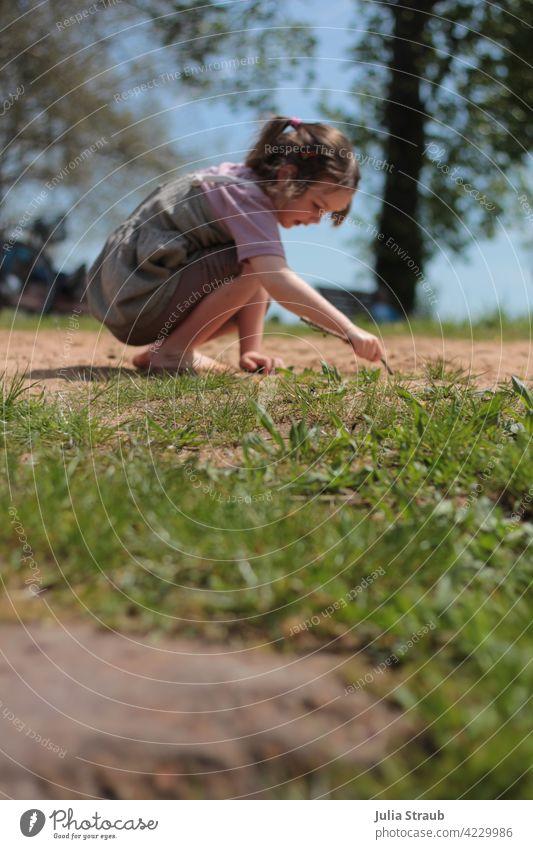 Mädchen zeichnet im Sand Spielen draußen sein Wiese Gras Barfuß Kleid T-Shirt Zopf Stock schreiben zeichnen malen deuten Sommer Frühling Sonne Sonnenschein
