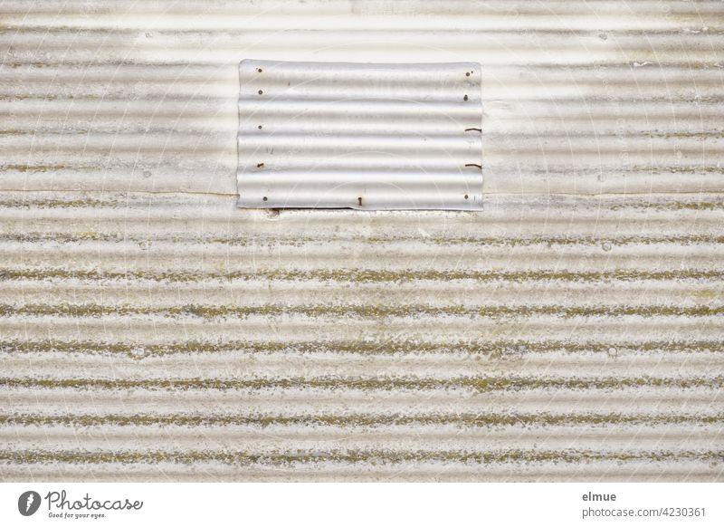 Eine kleine graue Wellblechplatte wurde mit Nägeln unfachmännisch an einer Faserzementplatte befestigt und verdeckt eine Öffnung Nagel Eternit Fassadenplatte