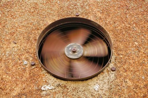 sich drehendes Rad eines alten, rostigen Wandlüfters in einer rostfabenen Wand / Physik / Ventilator / Rotation Wandventilator Lüfterrad integriert