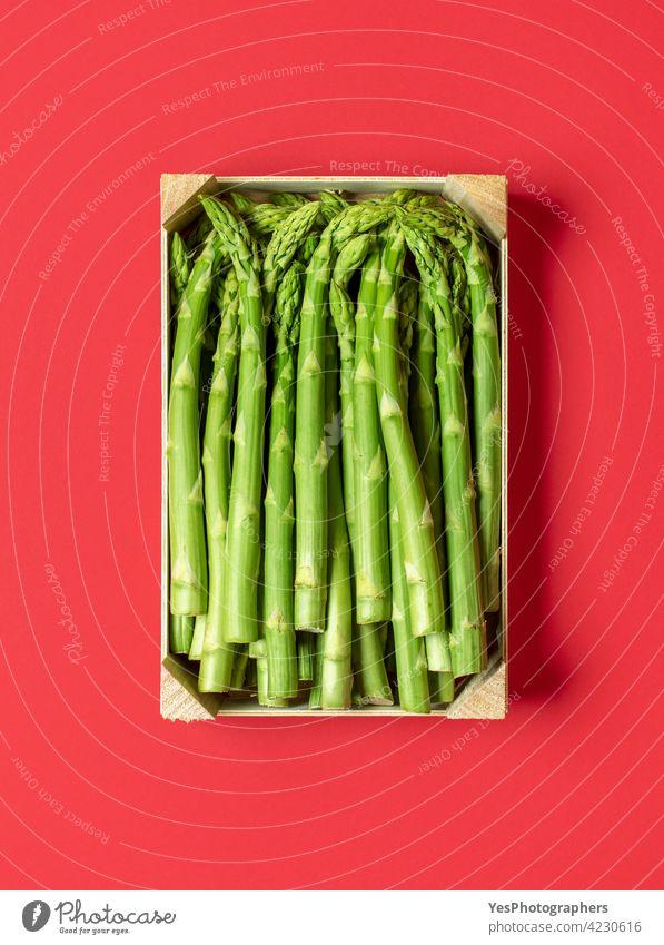 Grüner Spargel in einer Holzkiste in der Draufsicht, isoliert auf einem roten Hintergrund. oben Ackerbau Biografie Kasten Haufen Farbe Essen zubereiten Kiste