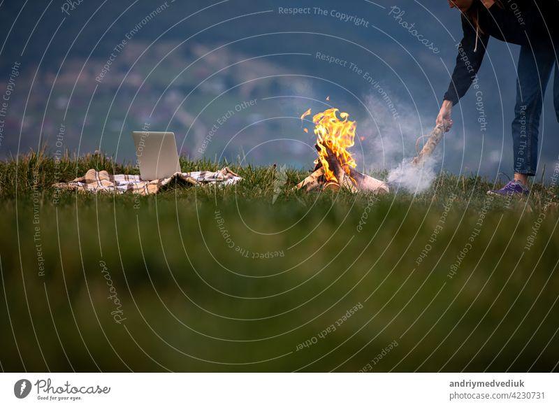 junge Frau Freiberufler wirft Brennholz in ein Feuer in den Bergen am Abend. Tourist Mädchen ruht und arbeitet im Freien Laptop Sitzen außerhalb reisen