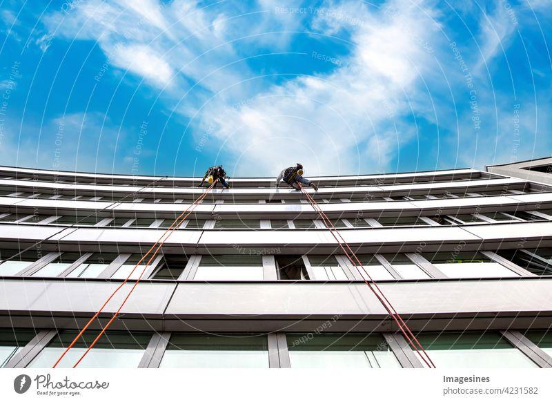 Fensterputzer! Zwei männliche industrielle Kletterer putzen Fenster an einem Gebäude. hoch in der Luft gegen blauen Wolkenhimmel hoch oben Himmel Erwachsener