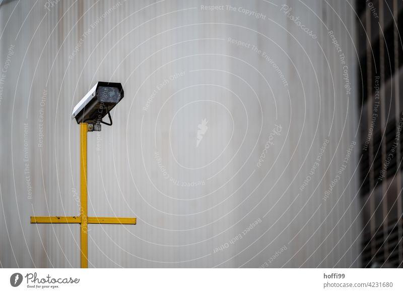 Überwachungskamera auf gelben Kreuz Fotokamera Kontrolle Überwachungsstaat Überwachungsgerät Fassade Technik & Technologie überwachen Video beobachten Macht