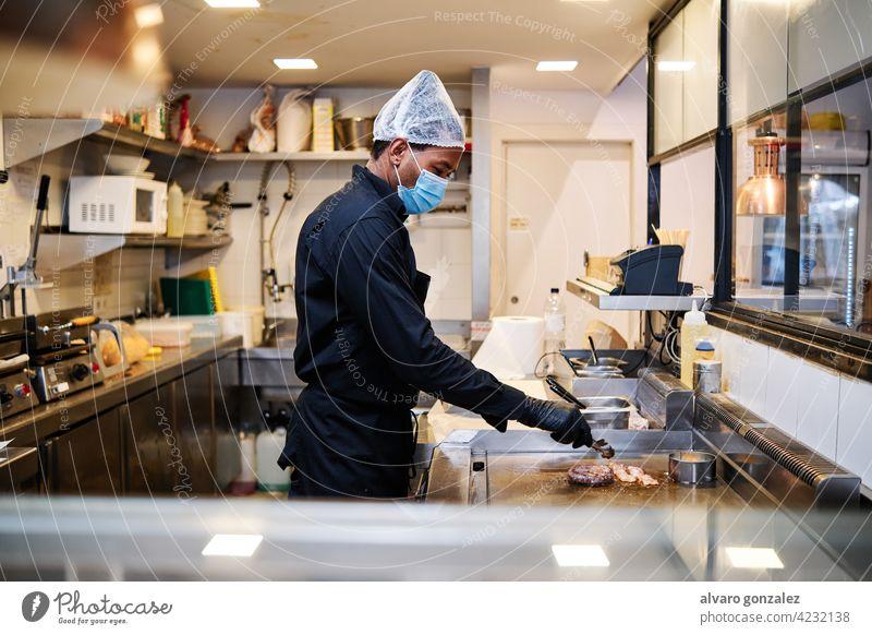 Nahaufnahme von professionellen lateinischen Koch Mann trägt eine Schutzmaske und Uniform bei der Arbeit im Restaurant Küche. Chef Kocher schützend Mundschutz