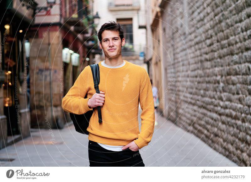 Porträt eines jungen Mannes, der im Freien auf der Straße steht. urban Großstadt Selbstvertrauen Rucksack Stehen posierend stylisch Beteiligung Schüler Blick
