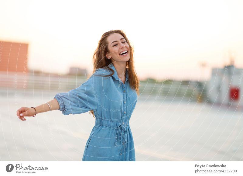 Porträt einer jungen Frau auf einem Dach, die den Sonnenuntergang genießt selbstbewusst Lächeln attraktiv schön junger Erwachsener Freude positiv Inhalt Stehen