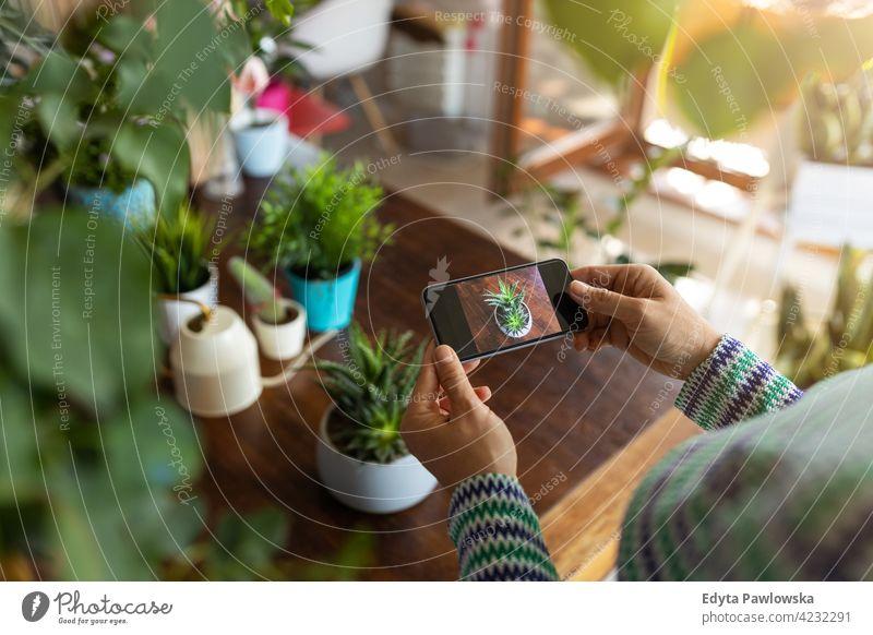 YoWoman fotografiert eine Topfpflanze mit ihrem Smartphone Floristik Pflege Gesundheit Blüte Gartenbau Flora botanisch Dekoration & Verzierung Botanik wachsen