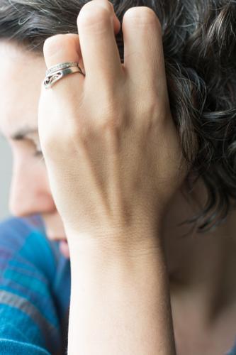 40 Jahre alte Frau, die ihr ergrautes, lockiges Haar berührt; eine Frau, die ihre natürliche Haarfarbe umarmt und ohne Farbstoffe auskommt Behaarung Haarpflege